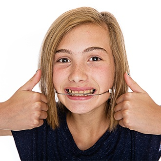 Preteen girl with headgear smiling