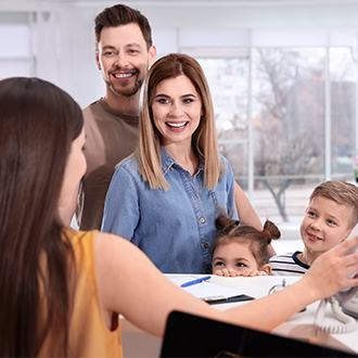 Family checking in at orthodontic office reception desk