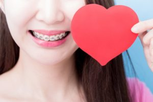 Young woman with braces in Holliston smiles with paper heart